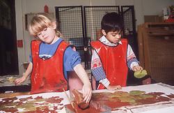 Junior school children wearing aprons painting with sponges in art class,