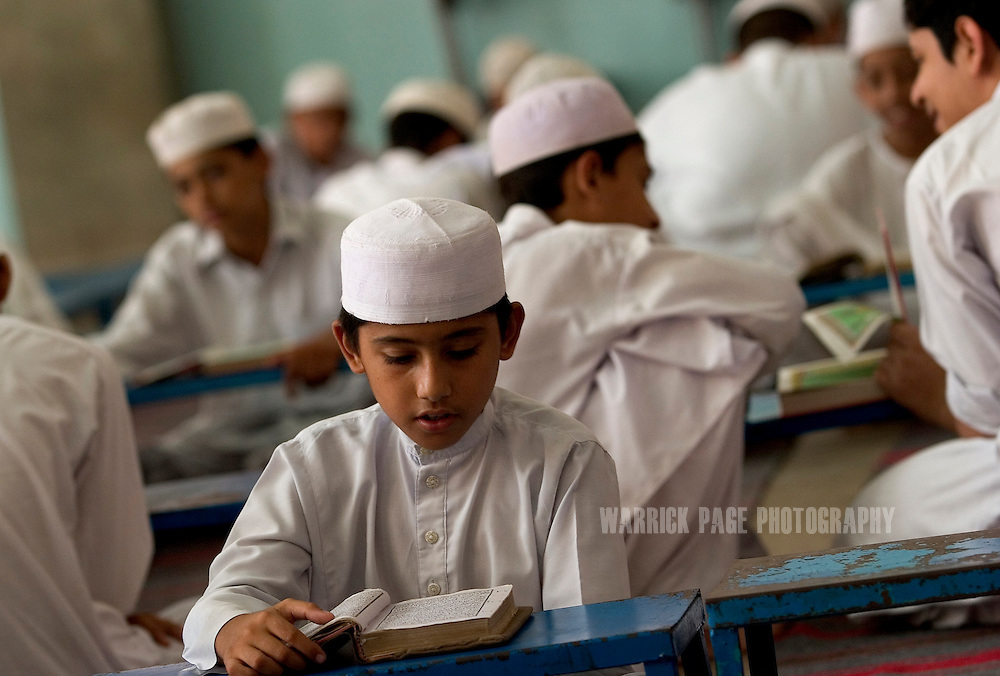 LAHORE, PAKISTAN - AUGUST 13: Students learn to study and recite the Koran at the Jamia Naeemia Madrassah (Madrasa), August 13, 2006, Lahore, Pakistan. Twenty-three suspects, mostly British-born of Pakistani origin, were arrested throughout England last week after a suspect detained in Pakistani tipped- off intelligence personnel about an impending terrorist plot to use liquid explosives to bring down trans-Atlantic commercial airlines in mid-journey. UK and US intelligence officials believe the suspects intended to conduct their operations to coincide with the fifth anniversary of the September 11, 2001 attack. Pakistan has been under intense pressure from the international community to stamp out terrorism after it was discovered suicide bombers from the July 7, 2005 London attacks had travelled to Pakistan and possibly received training in fundamentalist madrassas. (Photo by Warrick Page)