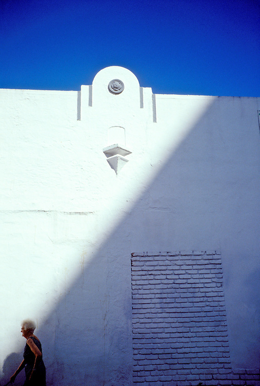 An elderly woman walking past an old, Art Deco building in trendy South Beach. This photo was made in November 1993, when many seniors still lived in the then rapidly gentrifying neighborhood. By 2000, South Beach was way more expensive, and the seniors were mostly gone.