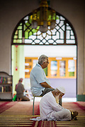 22 DECEMBER 2012 - SINGAPORE, SINGAPORE:  Men pray in the main prayer hall at the Sultan Mosque in Singapore. The Sultan Mosque is the focal point of the historic Kampong Glam area of Singapore. Also known as Masjid Sultan, it was named for Sultan Hussein Shah. The mosque was originally built in the 1820s. The original structure was demolished in 1924 to make way for the current building, which was completed in 1928. The mosque holds great significance for the Muslim community, and is considered the national mosque of Singapore. It was designated a national monument in 1975.           PHOTO BY JACK KURTZ
