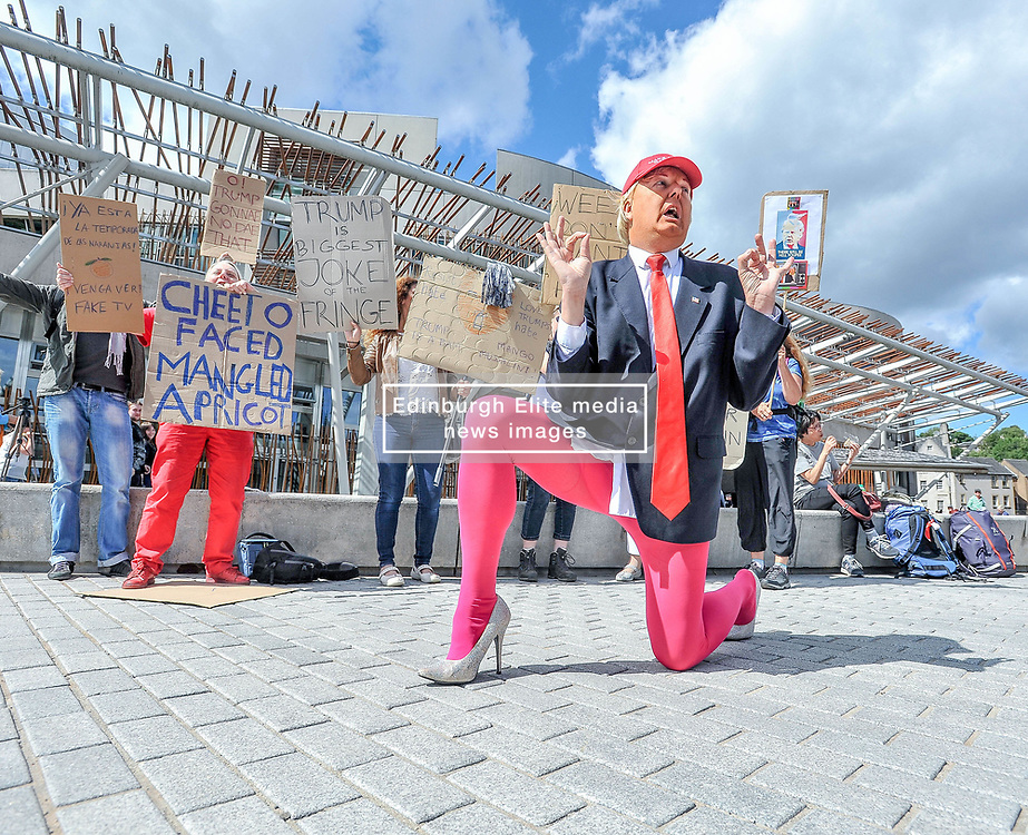 Roland Saunders as Donald Trump highlights his show outside the Scottish Parliament, aided by members of the public.<br /> <br /> © Dave Johnston/ EEm