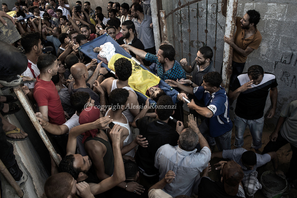 Gaza Strip: Palestinian mourners shout slogans during the funeral of four boys, all from the Bakr family, killed by Israeli naval bombardment, in Gaza City, on July 16, 2014. ALESSIO ROMENZI