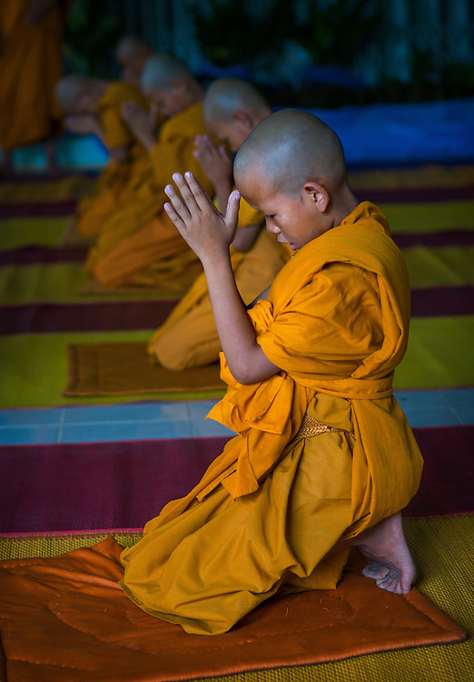 Young monks pray in Nakhon Nayok, Thailand