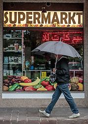 THEMENBILD - ein Mann spaziert mit einem Regenschirm vor dem Schaufenster des Helma Supermarktes - speziell für Arabische Touristen, aufgenommen am 22. Juni 2017, Kaprun, Österreich // A man walks with an umbrella in front of the shop window of the Helma supermarket - especially for Arab tourists in Kaprun, Austria on 2017/05/22. EXPA Pictures © 2017, PhotoCredit: EXPA/ JFK