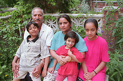 Mother and father outdoors in garden with daughters and son,