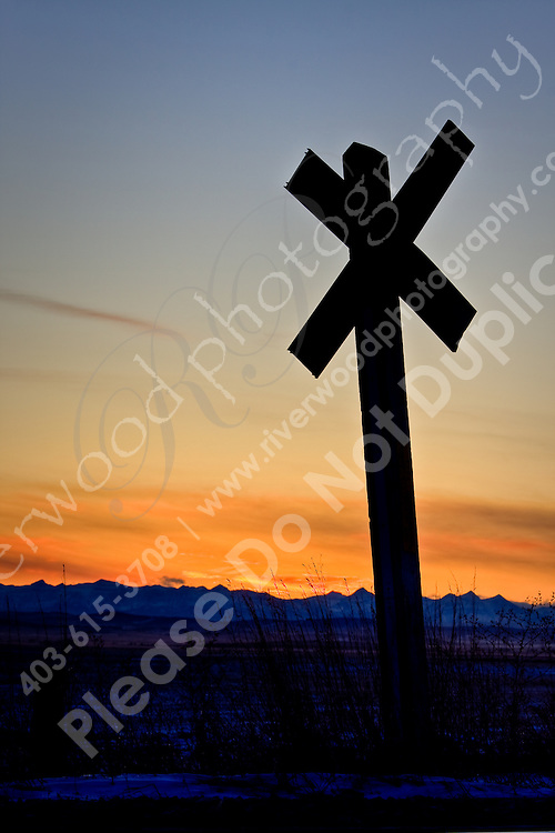 A railway crossing sillhouetted against the sunset over the Rocky Mountains.  East of Calgary near Indus, Alberta, Canada...©2008, Sean Phillips.http://www.Sean-Phillips.com
