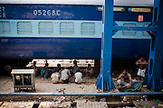 People rest in the shade of a train parked on the tracks in the New Delhi station on 7th July 2009.. .6318 / Himsagar Express, India's longest single train journey, spanning 3720 kms, going from the mountains (Hima) to the seas (Sagar), from Jammu and Kashmir state of the Indian Himalayas to Kanyakumari, which is the southern most tip of India...Photo by Suzanne Lee / for The National