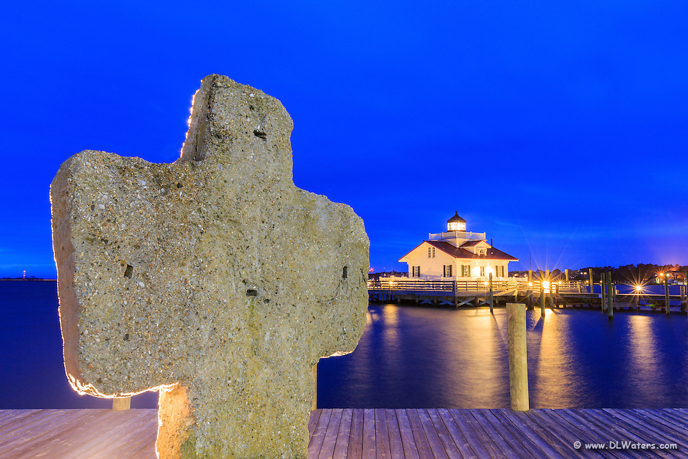 A commemorative cross overlooking the harbor and Roanoke Marshes  Lighthouse, photographed at twilight.
