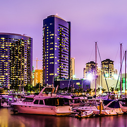 San Diego panorama photography of the San Diego skyline at night at Embarcadero Marina. Panoramic photo ratio is 1:3 with a purple tone. San Diego is a major city in Southern California in the United States.