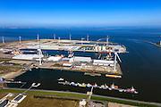 Nederland, Groningen, Eemshaven, 01-05-2013; ingang van de haven. Van boven naar beneden Beatrixhaven, in het midden de Julianahaven (met silo's van Holland Malt). In voorgrond de Emmahaven, met naast transportbedrijf Wagenborg opslag van onderdelen voor de assemblage (samen te stellen) van offshore windturbines zoals  masten, de turbine en de wieken, z.g.  superwindmolens met een enorm vermogen ook wel mega-windturbines. Een blauwe Waddenzee. .Port of Eemshaven with storage of parts for the assembly of offshore wind turbines such as masts, the turbine and blades (sails). A blue Wadden Sea..luchtfoto (toeslag op standard tarieven).aerial photo (additional fee required).copyright foto/photo Siebe Swart