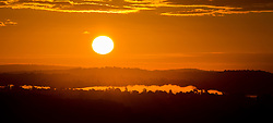 © Licensed to London News Pictures. 23/09/2016. Dorking, UK.  Early morning mist lies over Surrey at sunrise - seen from Box Hill on the second day of Autumn. Photo credit: Peter Macdiarmid/LNP