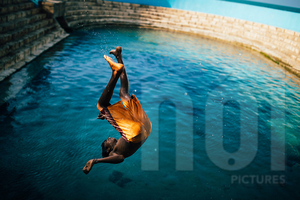 Young boys backflips in the waters of the Keerimalai Springs, sacred pools fed by sea waters on the northern shores of the Jaffna Peninsula, Sri Lanka, Asia
