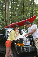 Couple observing map on car bonnet in forest