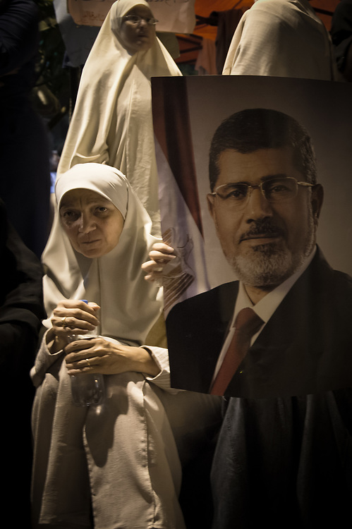 A supporter of Morsi sits next to a poster of Morsi during a sit-in on Rabaa Al-Adawiya Square Cairo, Egypt, July 5, 2013