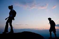 A couple hikes at sunset on the summit of Mount Monadnock in Monadnock State Park in Jaffrey, New Hampshire.