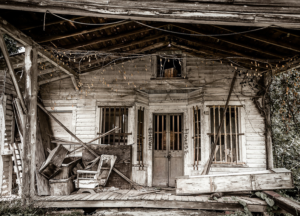 A cluttered front porch of an abandoned house on Highway 150 in Caswell County.