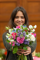 © Licensed to London News Pictures. 03/06/2016. London, UK. A member from Electric Daisy Flower Farm holds up a bouquet at the second annual London Rose Show, hosted by the Royal Horticultural Society, which opened at the Horticultural Halls in Victoria, where rose growers are showing off their latest blooms. Photo credit : Stephen Chung/LNP