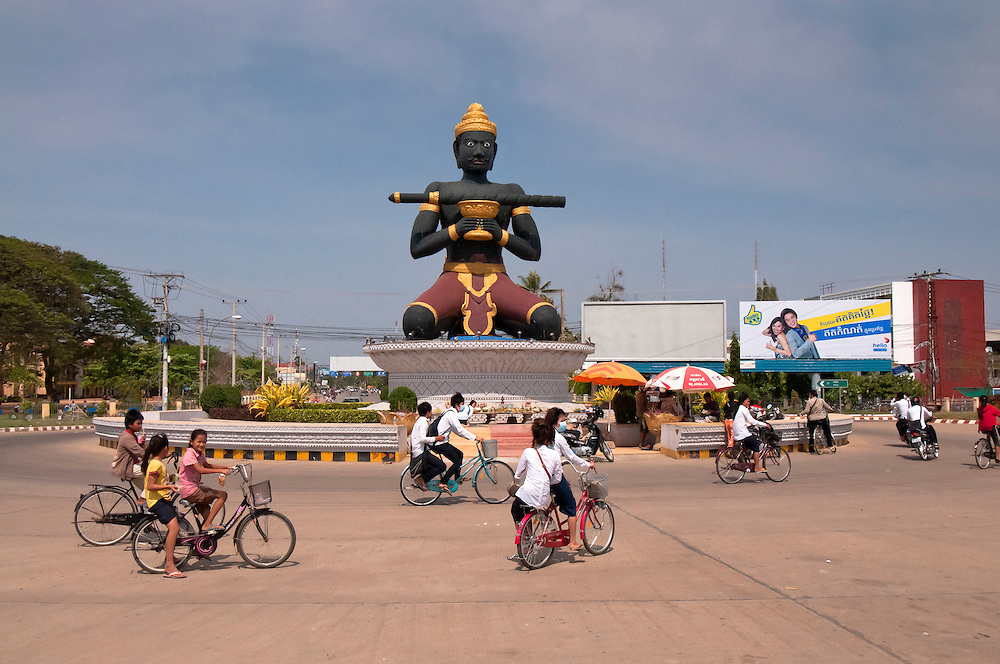 Children ride to school at the city entrance to Battambang, Cambodia.