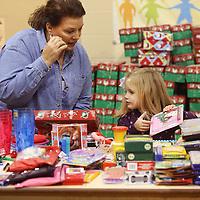 Adam Robison | BUY AT PHOTOS.DJOURNAL.COM<br /> St. Luke United Methodist Church member Rhonda Bennett helps Ava Turner, 4, pack a shoe box for a little girl Wednesday night.