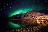 The Aurora Borealis (Northern Lights) reflecting on the water at Ersfjordbotn in Tromso, Norway.