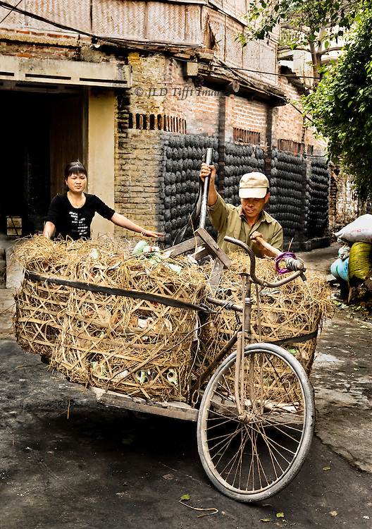 Young woman, supervisor, assists a laborer wtih huge barrels of pottery jars packed in straw, loaded on a bicycle adapted for the purpose.  Her arms are outstretched as though to help balance the heavy load on the light bicycle.