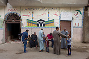 Neighbours hold an informal meeting under Islamic murals in a street of the village of Bairat on the West Bank of Luxor, Nile Valley, Egypt.