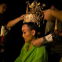 BEIJING, MAY -7, 2012 :  helpers adjust a crown on a models' head. .  ..Guo Pei , 45, is China's answer to haute couture. When she started out 15 years ago, there was no fashion in China .  Since then though  about everything in China has changed. Many more people are able to afford luxury products, and Chinese women, at least those who can afford it, follow international fashion trends. What makes Guo Pei different is what she puts on a runway. She employs 300 people in a workroom two hours from Beijing. She had to train them, but it?s also true that her creative freedom is tethered to relatively cheap labor. One dress alone, made entirely of golden panels, took 50,000 hours to embroider.