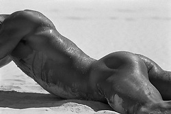 detail of a hot nude man in sand