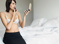 Young woman in underwear sitting on bed applying make-up