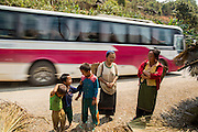 10 MARCH 2013 - ALONG HIGHWAY 13, LAOS:  Hmong women talk while a tour bus passes them on Highway 13. The paving of Highway 13 from Vientiane to near the Chinese border has changed the way of life in rural Laos. Villagers near Luang Prabang used to have to take unreliable boats that took three hours round trip to get from the homes to the tourist center of Luang Prabang, now they take a 40 minute round trip bus ride. North of Luang Prabang, paving the highway has been an opportunity for China to use Laos as a transshipping point. Chinese merchandise now goes through Laos to Thailand where it's put on Thai trains and taken to the deep water port east of Bangkok. The Chinese have also expanded their economic empire into Laos. Chinese hotels and businesses are common in northern Laos and in some cities, like Oudomxay, are now up to 40% percent. As the roads are paved, more people move away from their traditional homes in the mountains of Laos and crowd the side of the road living off tourists' and truck drivers.    PHOTO BY JACK KURTZ
