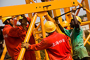 A Guinean worker and his Chinese co-workers assemble a crane at the construction site of a new 50,000-seat sports stadium in Conakry, Guinea on Friday March 6, 2009.  The project, an investment of about USD 50 million, is a gift to Guinea from the Chinese government.(Olivier Asselin for the New York Times).