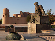 Low angle view of Statue of Muhammad ibn Musa Al-Khwarizmi (c.780-c.850), astronomer and mathematician, with main gate of Ichan-Kala, Ota Darvoza (Father Gate), and walls of the old city in the background, Khiva, Uzbekistan, pictured on July 6, 2010, in the afternoon. Khiva's old city, Ichan Kala, is surrounded by 2.2 kilometres of crenellated and bastioned city walls. Some sections may be 5th century, but the strongest sections were built 1686-88 by Arang Khan. The main gate today is the restored western Ota Darvoza (Father Gate). Khiva, ancient and remote, is the most intact Silk Road city. Ichan Kala, its old town, was the first site in Uzbekistan to become a World Heritage Site(1991). Picture by Manuel Cohen.
