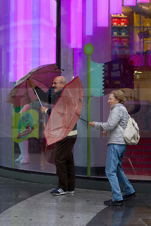 © Licensed to London News Pictures. 24/09/2012. LONDON, UK. Members of the public fight to keep their  umbrellas under control as they attempt to stay dry in central London today (24/09/12). Rain and strong winds today hit the UK causing widespread disruption with gusts of up to 60mph predicted for the north of England and up to 80mm of rain predicted in some areas.. Photo credit: Matt Cetti-Roberts/LNP