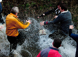 "© under license to London News Pictures. 8/3/11. Players scramble to get the ball from the river as it is freed from the scrum. The Derbyshire town of Ashbourne is besieged by hoards of people as the traditional game of Shrovetide football is played out across the town. Consisting of two teams the ""Upards"" and the ""Downards""; with goal posts two miles apart. Local history has it that the game has been played since the 12th Century. Pictured: WHSmith frontage boarded up. Picture credit should read Sam Spickett/LNP"