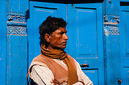 A stoic man folding his arms stands next to a blue doorway as he waits for the merchant to open for business in the Thamel District in Kathmandu, Nepal.
