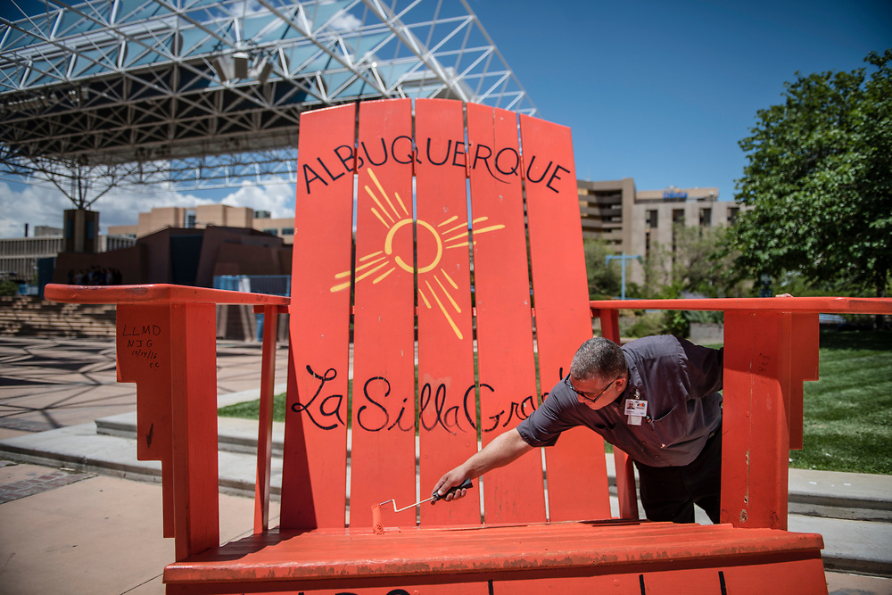 rer071317h/metro/July 13, 2017/Albuquerque Journal<br /> Robert Matos(Cq) a maintenance engineer with the Convention downtown  applies a fresh coat of paint on one of the most popular attractions in downtown Albuquerque at the Harry E. Kinney Civic Plaza.  Popular with out of town visitors, this larger than life adirondack chair called La Silla Grande has provided the perfect backdrop for taking selfies in the Duke city. <br /> Albuquerque, New Mexico Roberto E. Rosales/Albuquerque Journal