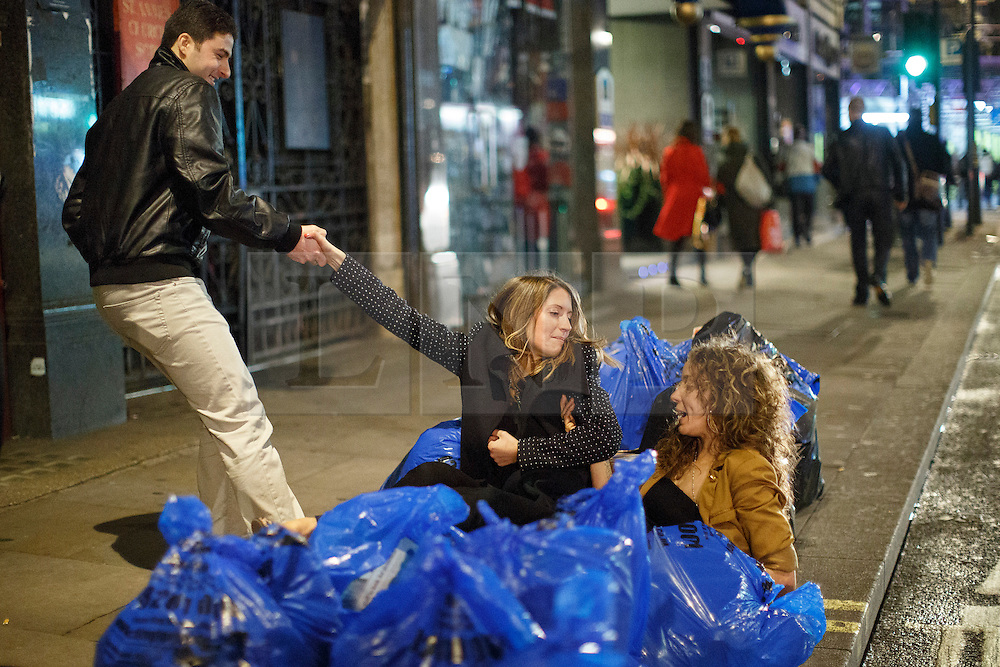 """© licensed to London News Pictures. London, UK 14/12/2013. """"Mad Friday"""" revellers fall on some bin bags in Soho, London whilst enjoying the last Friday night out before Christmas, which is also the busiest night of the year for emergency services. Photo credit: Tolga Akmen/LNP"""