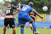 Bayo Akinfenwa forward for AFC Wimbledon (10) and Matt Partridge defender for Newport County (21) tussle during the Sky Bet League 2 match between AFC Wimbledon and Newport County at the Cherry Red Records Stadium, Kingston, England on 7 May 2016. Photo by Stuart Butcher.