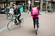 In Utrecht passeren bezorgers van Foodora en Deliveroo elkaar. Foodora en Deliveroo zijn concurrerende bezorgdiensten voor restaurants en cateringbedrijven en richt zich met name op kwaliteitsrestaurants. De bezorgers, drivers genaamd, rijden doorgaans op hun eigen fiets.<br /> <br /> In Utrecht messengers for Foodora and Deliveroo passes each other. Foodora and Deliveroo are concurrent delivery services for restaurants and catering firms and focuses on quality restaurants. The bike messengers usually ride on their own bike.