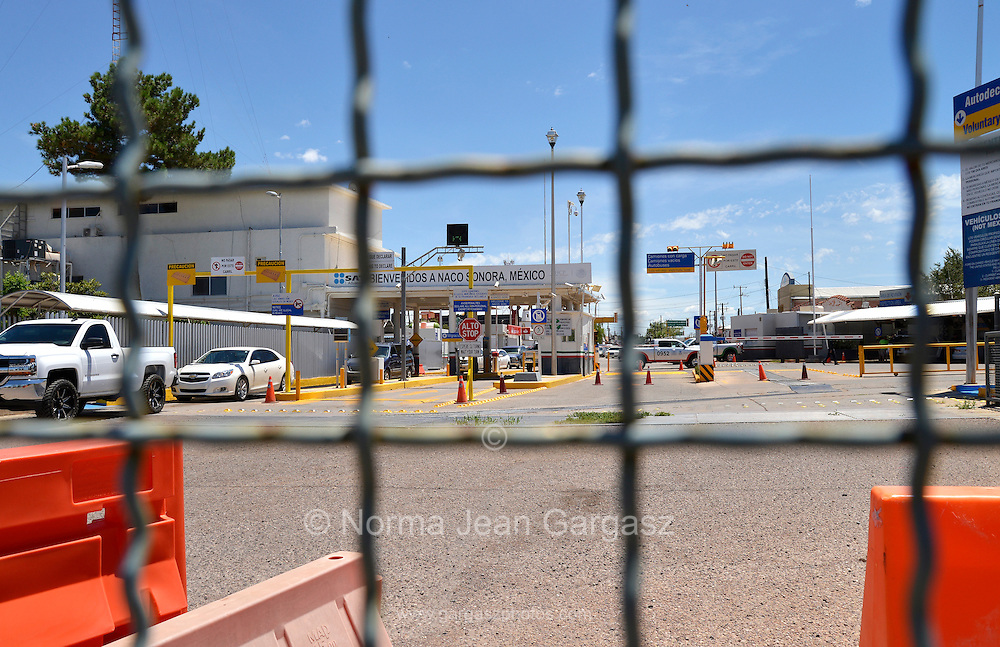 Vehicles exit the inspection station in Naco, Sonora, Mexico, and head north to enter the port-of-entry in Naco, Arizona, USA, as seen from Arizona. The international border between Naco, Arizona, USA and Naco, Sonora, Mexico is indicated by a metal wall, which extends to the east and west of the ports-of-entry.
