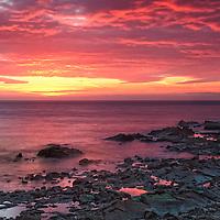 The rising sun sets the sky ablaze over the Irish Sea and Dublin Bay, Dublin, Ireland.
