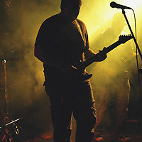 Silhouette of man playing an electric guitar on stage.