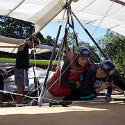 A tandem hang glider passenger receives instructions from the pilot before take off from the hillside of Pedro Bonita high in the hills of Rio de Janeiro. Pilots of hang gliders and para gliders take tourists for tandem flights with breathtaking views of the city before landing on Sao Conrado beach. Rio de Janeiro,  Brazil. 9th September 2010. Photo Tim Clayton.