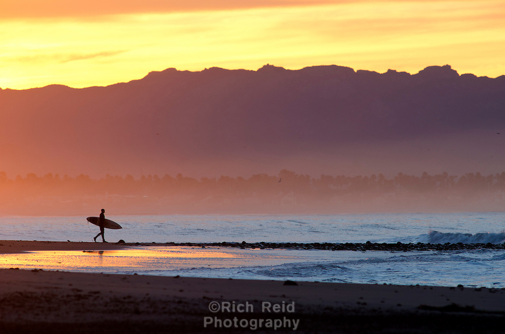 A surfer silhouetted below the Santa Monica Mountains at Surfers Point in Ventura, California.