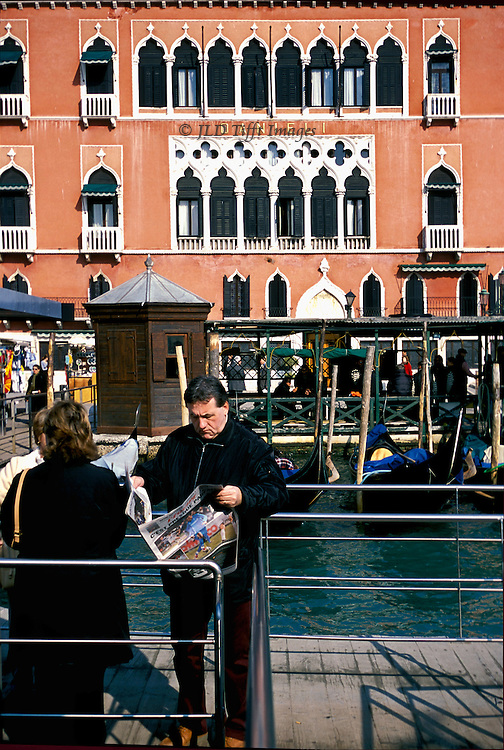 Vaporetto passenger reads newspaper while waiting on the dock of the Riva degli Schiavoni,opposite the  Hotel Danieli, Venice..