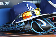 LOS ANGELES, CA - JUNE 17:  A baseball cap, glove, and sunglasses lie on the dugout bench during batting practice before the Los Angeles Dodgers game against the Colorado Rockies at Dodger Stadium on Tuesday, June 17, 2014 in Los Angeles, California. The Dodgers won the game 4-2. (Photo by Paul Spinelli/MLB Photos via Getty Images)