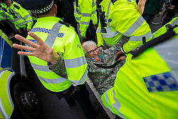 © Licensed to London News Pictures. 07/10/2019. London, UK. An Extinction Rebellion protester is carried away by police in Trafalgar Square. Photo credit: George Cracknell Wright/LNP