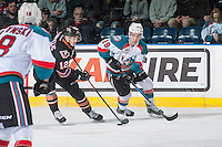 KELOWNA, CANADA - FEBRUARY 1: Dillon Dube #19 of the Kelowna Rockets checks Mark Kastelic #12 of the Calgary Hitmen as he skates with the puck on February 1, 2017 at Prospera Place in Kelowna, British Columbia, Canada.  (Photo by Marissa Baecker/Shoot the Breeze)  *** Local Caption ***