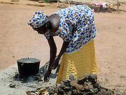 Senegal Lady cooking outside on open fire