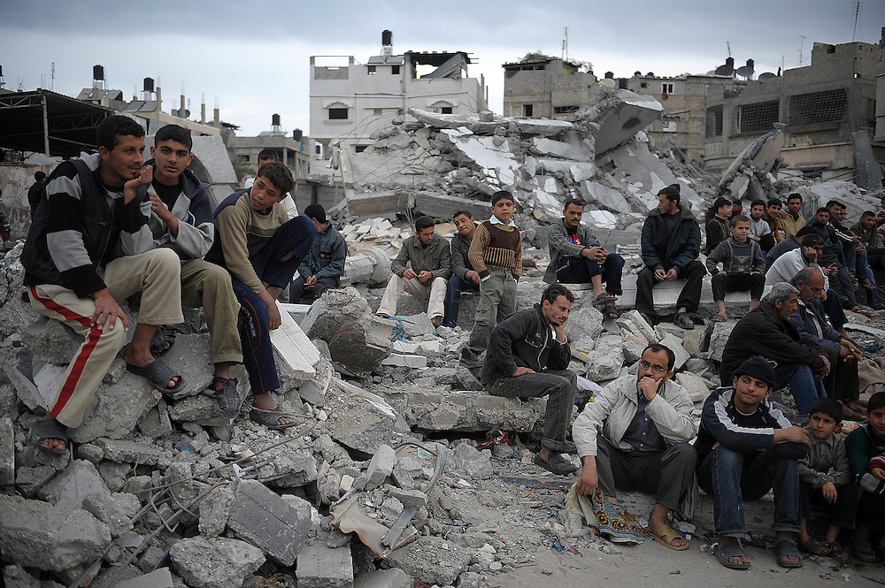 Palestinians wait to perform the Friday noon prayer on the rubble of an Israel-bombed mosque in Gaza City on January 23, 2009. Israeli Prime Minister Ehud Olmert has put the justice minister in charge of defending Israel against charges of war crimes during its 22-day Gaza assault. According to the Palestinian central bureau of statistics, 20 mosques were among the over 4000 buildings that were destroyed since the December 27 start of Israel's offensive.